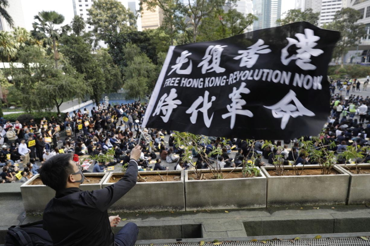A pro-democracy supporter waves a flag during a rally by the advertising industry in Hong Kong on Monday, Dec. 2, 2019. Thousands of people took to Hong Kong's streets Sunday in a new wave of pro-democracy protests, but police fired tear gas after some demonstrators hurled bricks and smoke bombs, breaking a rare pause in violence that has persisted during the six-month-long movement.
