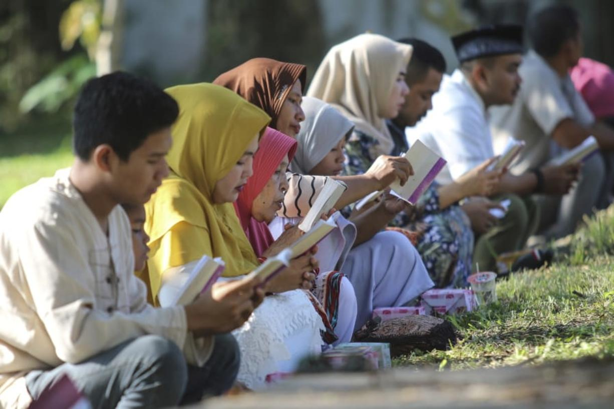 People read the holy book of the Quran as they pray at a mass grave site for the victims of the Indian Ocean tsunami, during the commemoration of the 15th anniversary of the disaster in Banda Aceh, Indonesia, Thursday, Dec. 26, 2019.