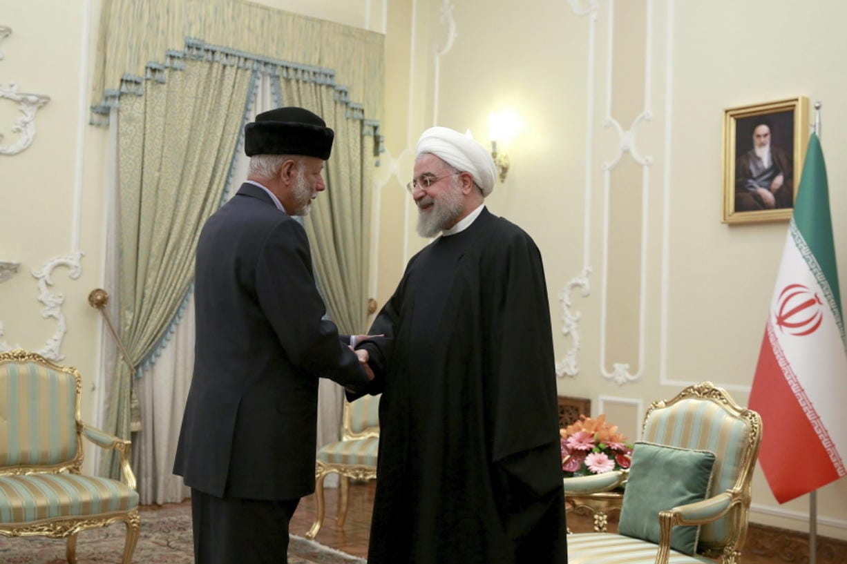 In this photo released by the official website of the office of the Iranian Presidency, President Hassan Rouhani, right, shakes hands with Omani Minister of State for Foreign Affairs Yusuf bin Alawi at the start of their meeting, in Tehran, Iran, Tuesday, Dec.