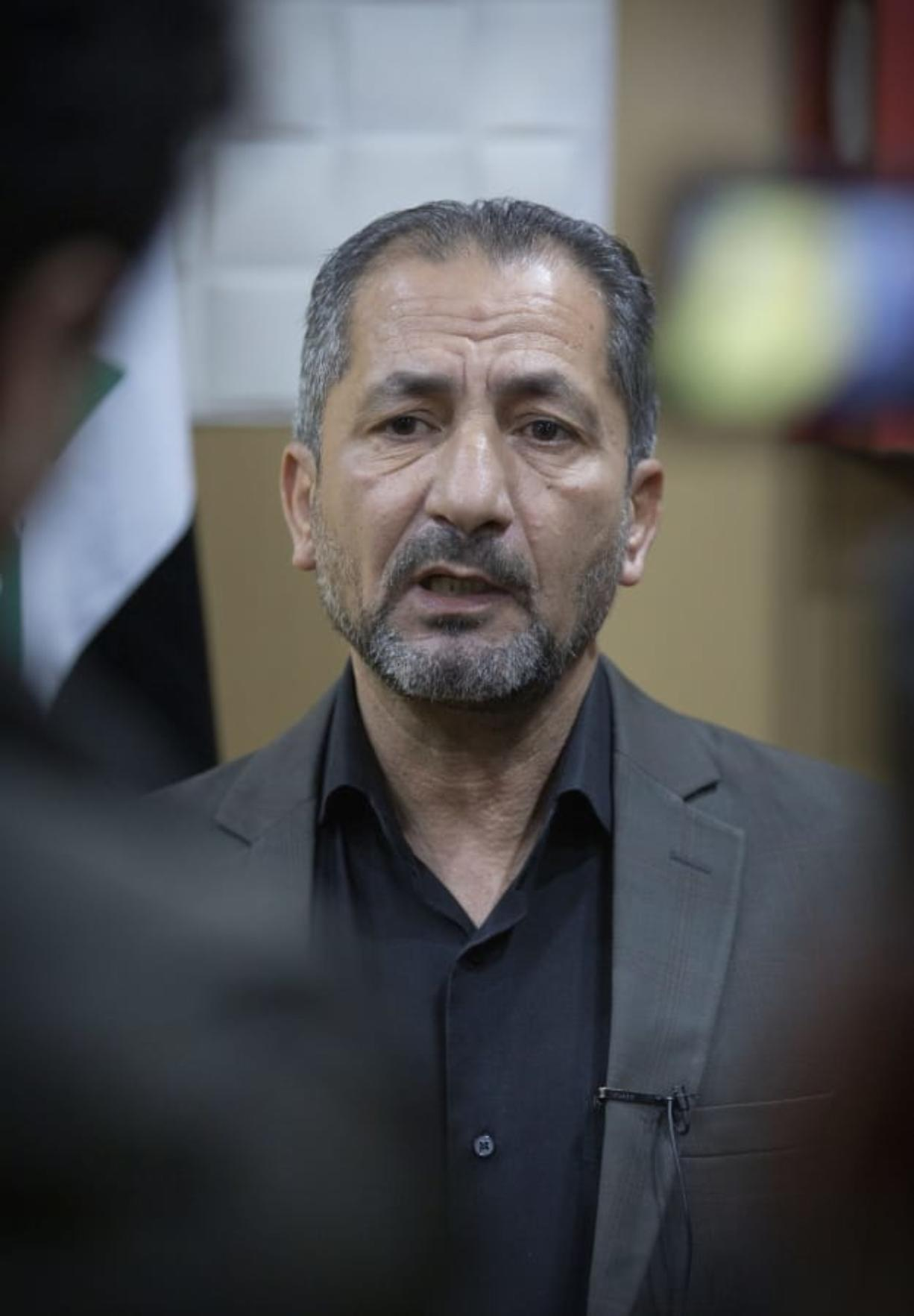 """Mohammed Mohieh, the spokesman of Iraq's Iranian-backed Kataeb Hezbollah, or Hezbollah Brigades, gives an interview at his office, in Baghdad, Iraq, Monday, Dec. 30, 2019. Mohieh said Monday that the death toll from U.S. military strikes in Iraq and Syria against its fighters has risen to 25, vowing to exact revenge for the """"aggression of evil American ravens."""" (AP Photo/Nasser Nasser)"""