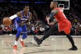 New York Knicks guard Frank Ntilikina, left, passes the ball around Portland Trail Blazers guard Damian Lillard during the first half of an NBA basketball game in Portland, Ore., Tuesday, Dec. 10, 2019. (AP Photo/Steve Dykes)