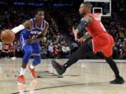 New York Knicks guard Frank Ntilikina, left, passes the ball around Portland Trail Blazers guard Damian Lillard during the first half of an NBA basketball game in Portland, Ore., Tuesday, Dec. 10, 2019.