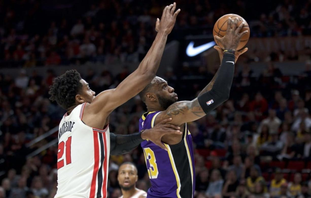 Los Angeles Lakers forward LeBron James, right, shoots in front of Portland Trail Blazers center Hassan Whiteside during the first half of an NBA basketball game in Portland, Ore., Saturday, Dec. 28, 2019.