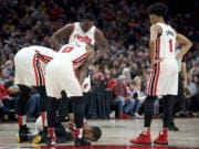Portland Trail Blazers guard Rodney Hood is surrounded by teammates after tearing his Achilles tendon during the first half of the team's NBA basketball game against the Los Angeles Lakers in Portland, Ore., Friday, Dec. 6, 2019.