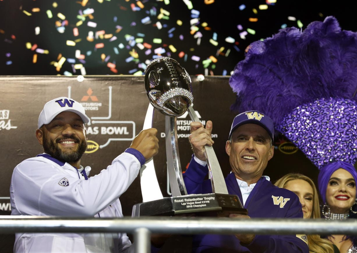 Jimmy Lake, left, Washington defensive coordinator and incoming head coach, and Washington head coach Chris Petersen pose with the Las Vegas Bowl trophy after they defeated Boise State in the Las Vegas Bowl NCAA college football game at Sam Boyd Stadium, Saturday, Dec. 21, 2019, in Las Vegas.