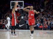 Portland Trail Blazers guard Kent Bazemore, right, and guard CJ McCollum react after Bazemore made a 3-point basket against the Orlando Magic during the second half of an NBA basketball game in Portland, Ore., Friday, Dec. 20, 2019.