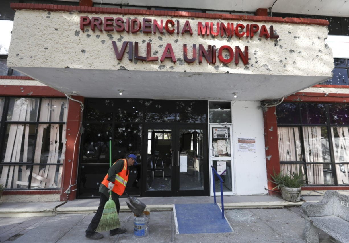 A worker cleans up Monday outside City Hall, riddled with bullet holes, in Villa Union, Mexico. (Eduardo Verdugo/Associated Press)