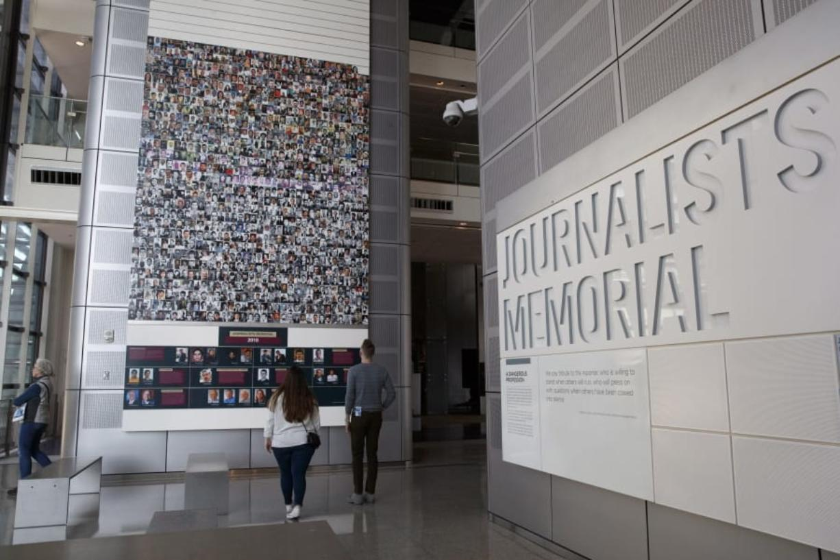 People visit the journalists memorial Friday at the Newseum in Washington. (Jacquelyn Martin/Associated Press)