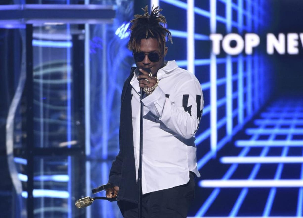 """FILE - In this May 1, 2019 file photo, Juice WRLD accepts the award for top new artist at the Billboard Music Awards at the MGM Grand Garden Arena in Las Vegas. The Chicago-area rapper, whose real name is Jarad A. Higgins, was pronounced dead Sunday, Dec. 8 after a """"medical emergency'' at Chicago's Midway International Airport, according to authorities. Chicago police said they're conducting a death investigation."""