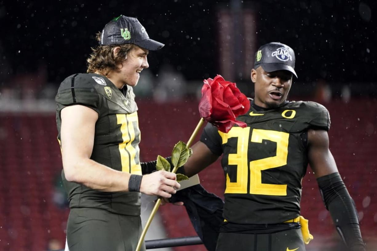 Oregon quarterback Justin Herbert (10) and teammate La'Mar Winston Jr. (32) celebrate after Oregon defeated Utah 37-15 in an NCAA college football game for the Pac-12 Conference championship in Santa Clara, Calif., Friday, Dec. 6, 2018.