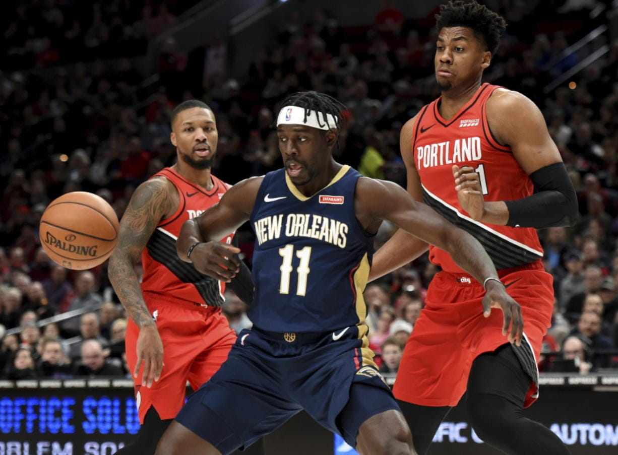 New Orleans Pelicans guard Jrue Holiday, center, loses control of the ball as Portland Trail Blazers guard Damian Lillard, left and center Hassan Whiteside, right, look on during the first half of an NBA basketball game in Portland, Ore., Monday, Dec. 23, 2019. The Blazers won 113-106.