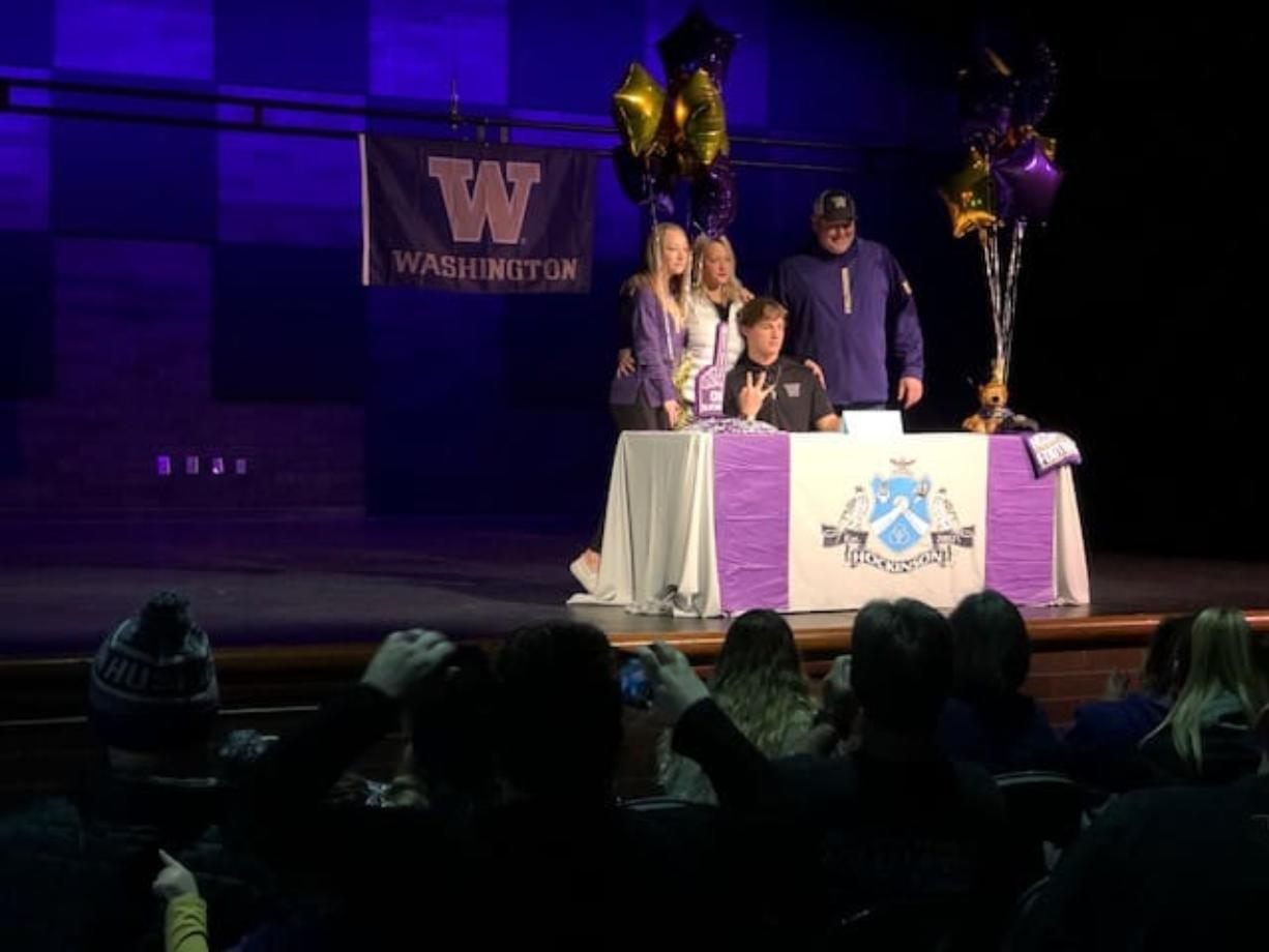 """Hockinson's Sawyer Racanelli holds up a """"W"""" while surrounded by his family after signing his National Letter of Intent to the University of Washington on Wednesday at Hockinson's auditorium."""