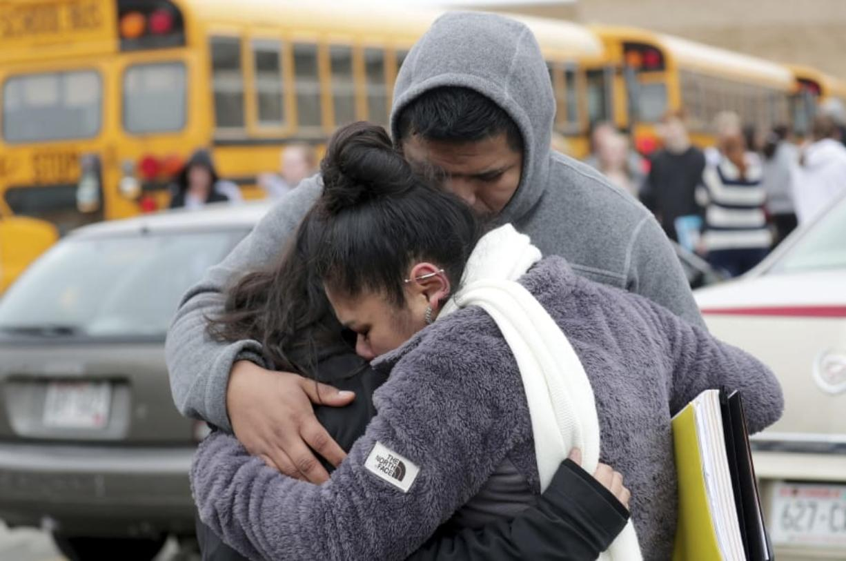 Becky Galvan, center, consoles her daughter, Ashley Galvan, a 15-year-old sophomore, with her father Jose Chavez outside Waukesha South High School in Waukesha on Monday, Dec. 2, 2019. Gunshots were exchanged between a student and a school resource officer inside Waukesha South High School, according to school officials. (Mike De Sisti/Milwaukee Journal-Sentinel via AP)