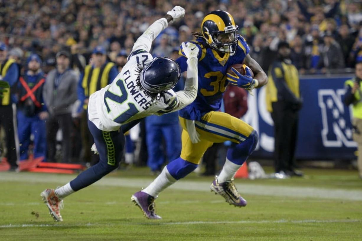 Los Angeles Rams running back Todd Gurley, right, scores past Seattle Seahawks cornerback Tre Flowers during the second half of an NFL football game Sunday, Dec. 8, 2019, in Los Angeles. (AP Photo/Kyusung Gong)