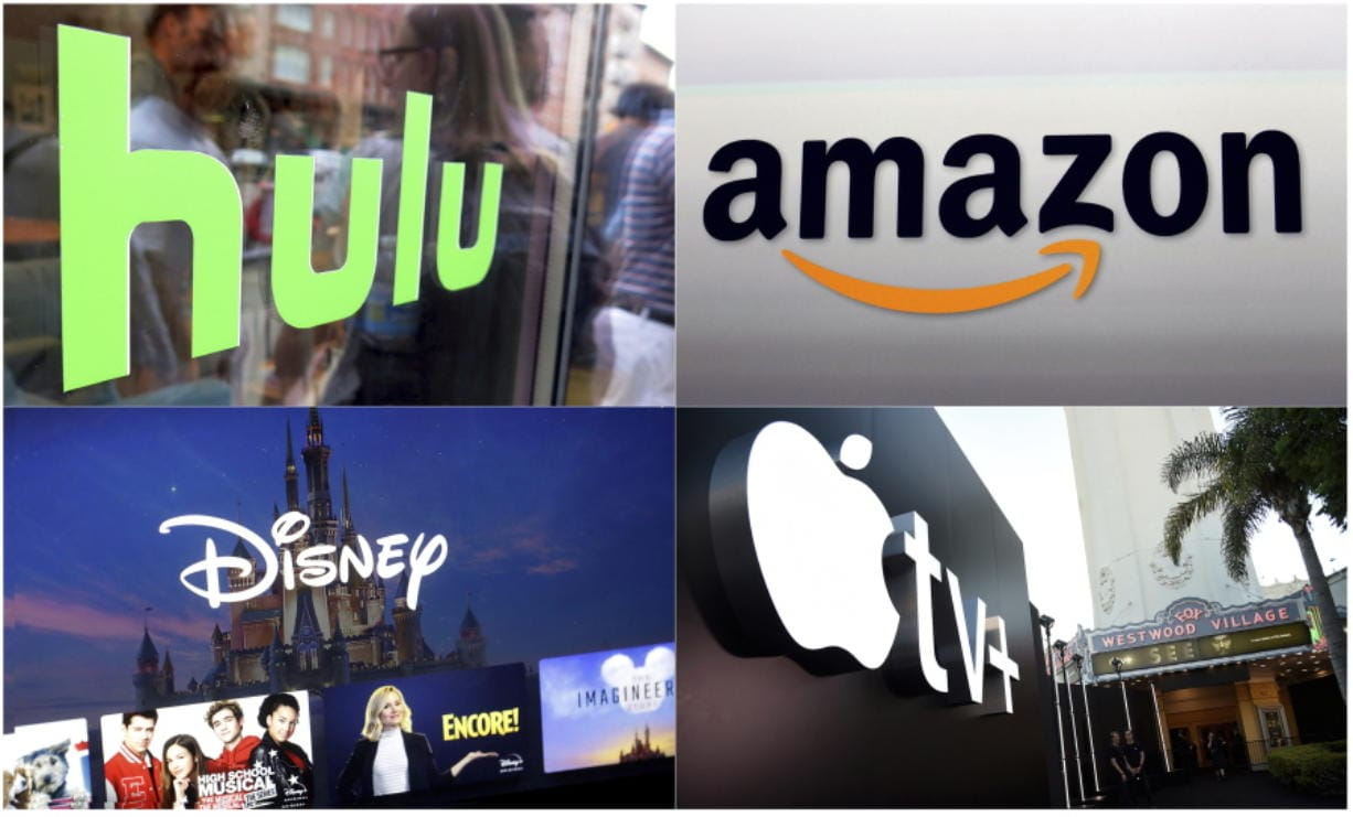 """This combination photo shows, clockwise from top left, the Hulu logo on a window at the Milk Studios space in New York, the Amazon logo in Santa Monica, Calif., the Apple TV+ logo displayed outside the Regency Village Theatre in Los Angeles before the premiere of the the Apple TV+ series """"See,"""" and a screen grab of the Disney Plus streaming service on a computer screen."""