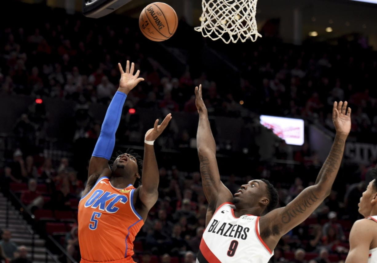 Oklahoma City Thunder guard Luguentz Dort, left, shoots the ball over Portland Trail Blazers forward Nassir Little, right, during the first half of an NBA basketball game in Portland, Ore., Sunday, Dec. 8, 2019.