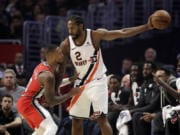 Portland Trail Blazers' Damian Lillard, left, defends on Los Angeles Clippers' Kawhi Leonard (2) during the first half of an NBA basketball game Tuesday, Dec. 3, 2019, in Los Angeles.