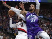 Portland Trail Blazers forward Carmelo Anthony (00) is fouled by Utah Jazz center Rudy Gobert (27) during the second quarter of an NBA basketball game, Thursday, Dec. 26, 2019, in Salt Lake City.