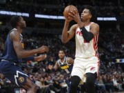 Portland Trail Blazers center Hassan Whiteside, right, shoots for a basket over Denver Nuggets forward Jerami Grant in the first half of an NBA basketball game Thursday, Dec. 12, 2019, in Denver.