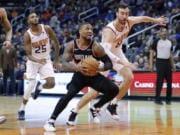 Portland Trail Blazers guard Damian Lillard drives past Phoenix Suns forward Frank Kaminsky (8) and forward Mikal Bridges (25) during the first half of an NBA basketball game, Monday, Dec. 16, 2019, in Phoenix.