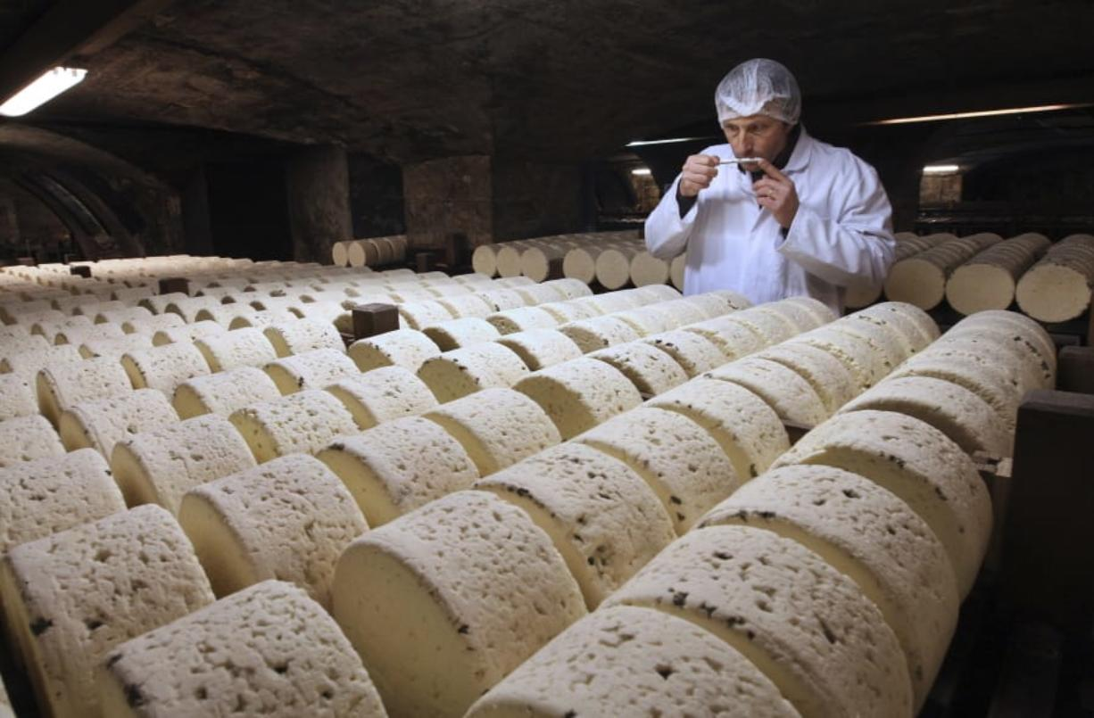 FILE - In this Jan. 21, 2009, file photo, Bernard Roques, a refiner of Societe company, smells a Roquefort cheese as they mature in a cellar in Roquefort, southwestern France. The Trump administration is proposing tariffs on up to $2.4 billion worth of French imports, from Roquefort cheese to handbags,  retaliation for France's tax on American tech giants like Google, Amazon and Facebook. The Office of the U.S. Trade Representative says France's new digital services tax discriminates against U.S.