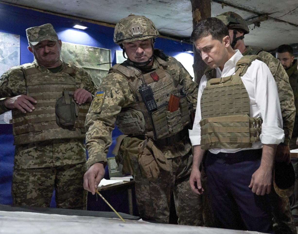 FILE - In this Oct. 14, 2019, file photo, Ukrainian President Volodymyr Zelenskiy, right, listens to a serviceman as he visits the war-hit Donetsk region, eastern Ukraine. For Zelenskiy, a summit meeting with Russia, France and Germany marks a decisive moment in his push to end more than five years of fighting with Moscow-backed separatists in the eastern part of his country.