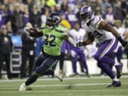 Seattle Seahawks' Chris Carson runs on a 26-yard carry as Minnesota Vikings' Danielle Hunter pursues during the second half of an NFL football game, Monday, Dec. 2, 2019, in Seattle. (AP Photo/Ted S.