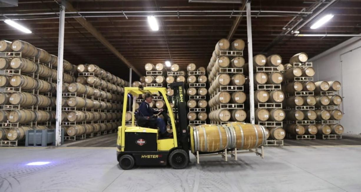 In this photo taken Thursday, Nov. 21, 2019, barrels of wine are moved into storage at Chateau Ste. Michelle winery in Woodinville, Wash. From less than 20 wineries in 1981, the Washington wine industry has grown to more than 1,000 this year. And the growth is likely to continue.