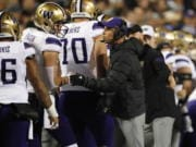 Washington quarterback Jacob Eason, left, confers with coach Chris Petersen during the first half of the team's NCAA college football game against Colorado on Saturday, Nov. 23, 2019, in Boulder, Colo.