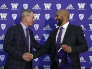 Washington NCAA college football head coach Chris Petersen, left, shakes hands with defensive coordinator Jimmy Lake following a news conference about Lake taking over the head coaching position, Tuesday, Dec. 3, 2019, in Seattle. Petersen unexpectedly resigned on Monday, a shocking announcement with the Huskies coming off a 7-5 regular season and bound for a sixth straight bowl game under his leadership. Petersen will coach Washington in a bowl game, his final game in charge.