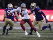 Washington State quarterback Anthony Gordon scrambles out of the pocket as he is chased by Washington linebacker Joe Tryon during the second half of an NCAA college football game, on Friday, Nov. 29, 2019 in Seattle. Washington won 31-13.