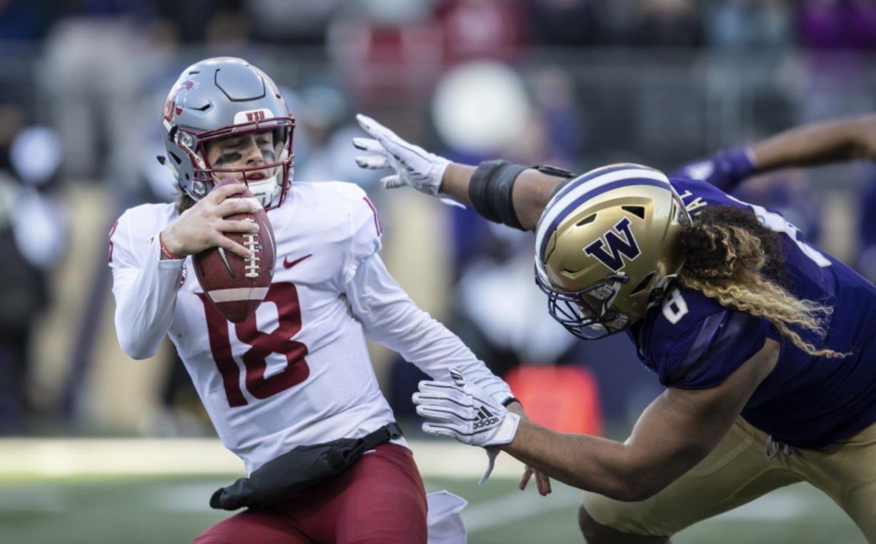 Washington State quarterback Anthony Gordon tries to escape the grasp of Washington defensive lineman Benning Potoa'e during the first half an NCAA college football game, on Friday, Nov. 29, 2019 in Seattle.