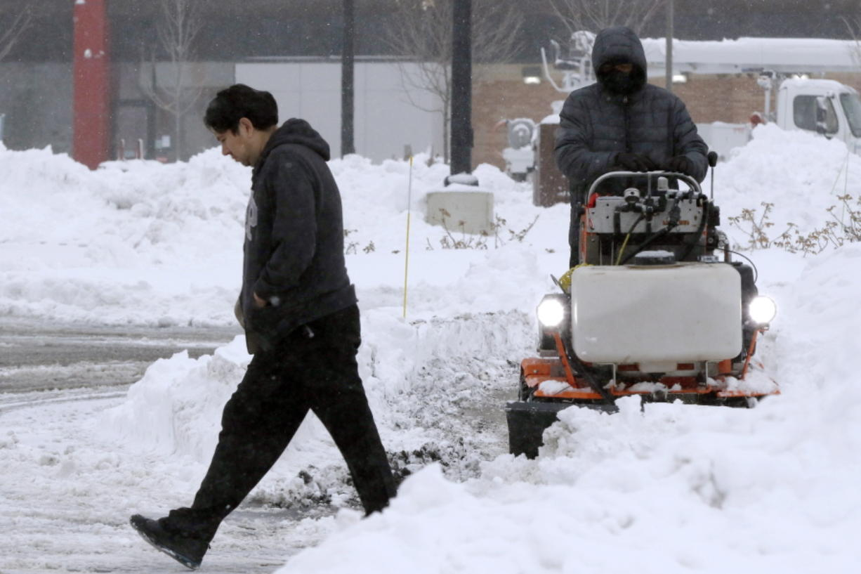 A pedestrian makes their way through a parking lot where snow is being cleared after an overnight snowfall, Monday, Dec. 2, 2019, in Marlborough, Mass. (AP Photo/Bill Sikes)