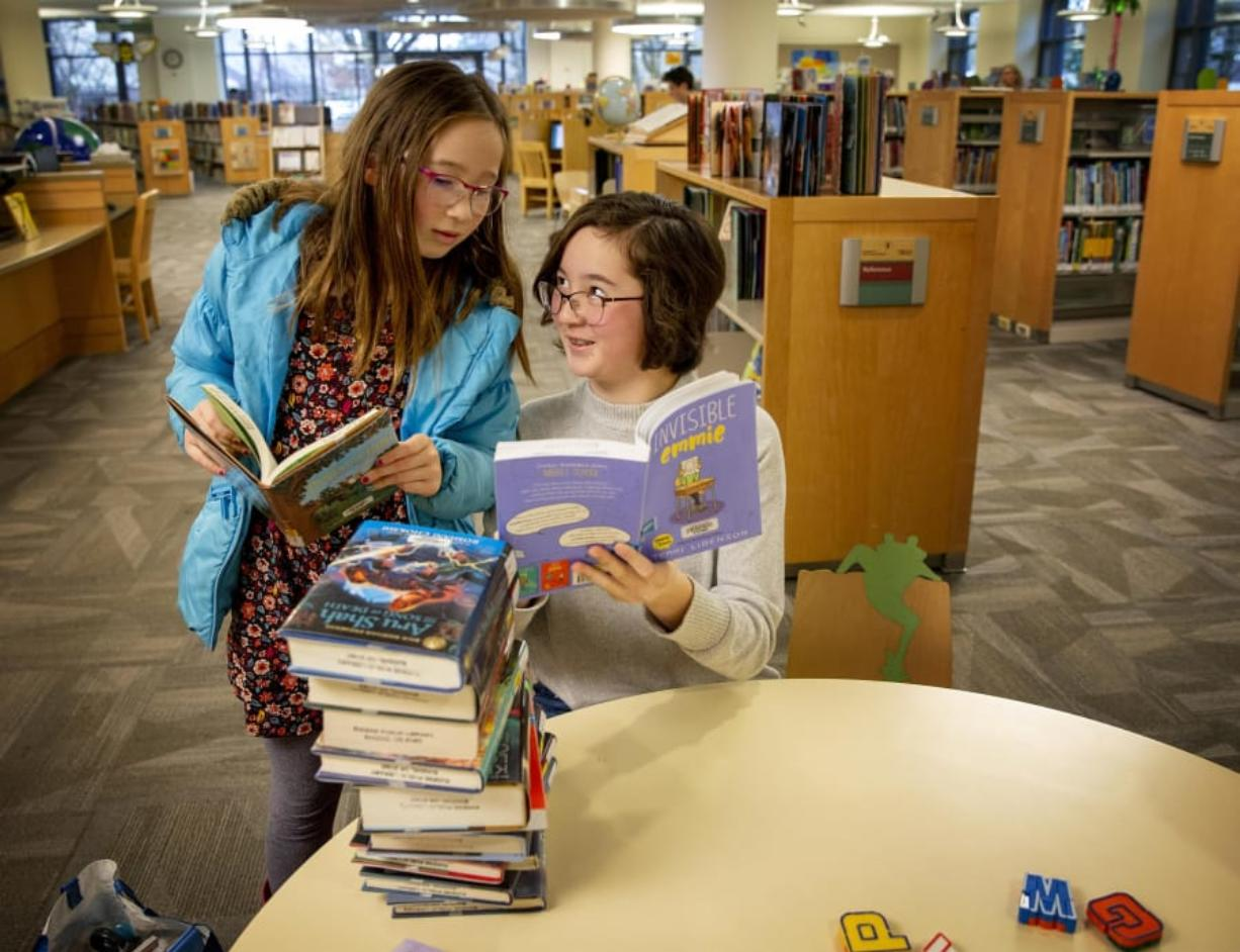 "Hannah Rhee, left, listens as her sister Maya Rhee tells her about a part of the story in the book ""Invisible Emmie"" while visiting the Eugene Public Library on Thursday. Maya is a voracious reader and had a stack of books ready to check out."