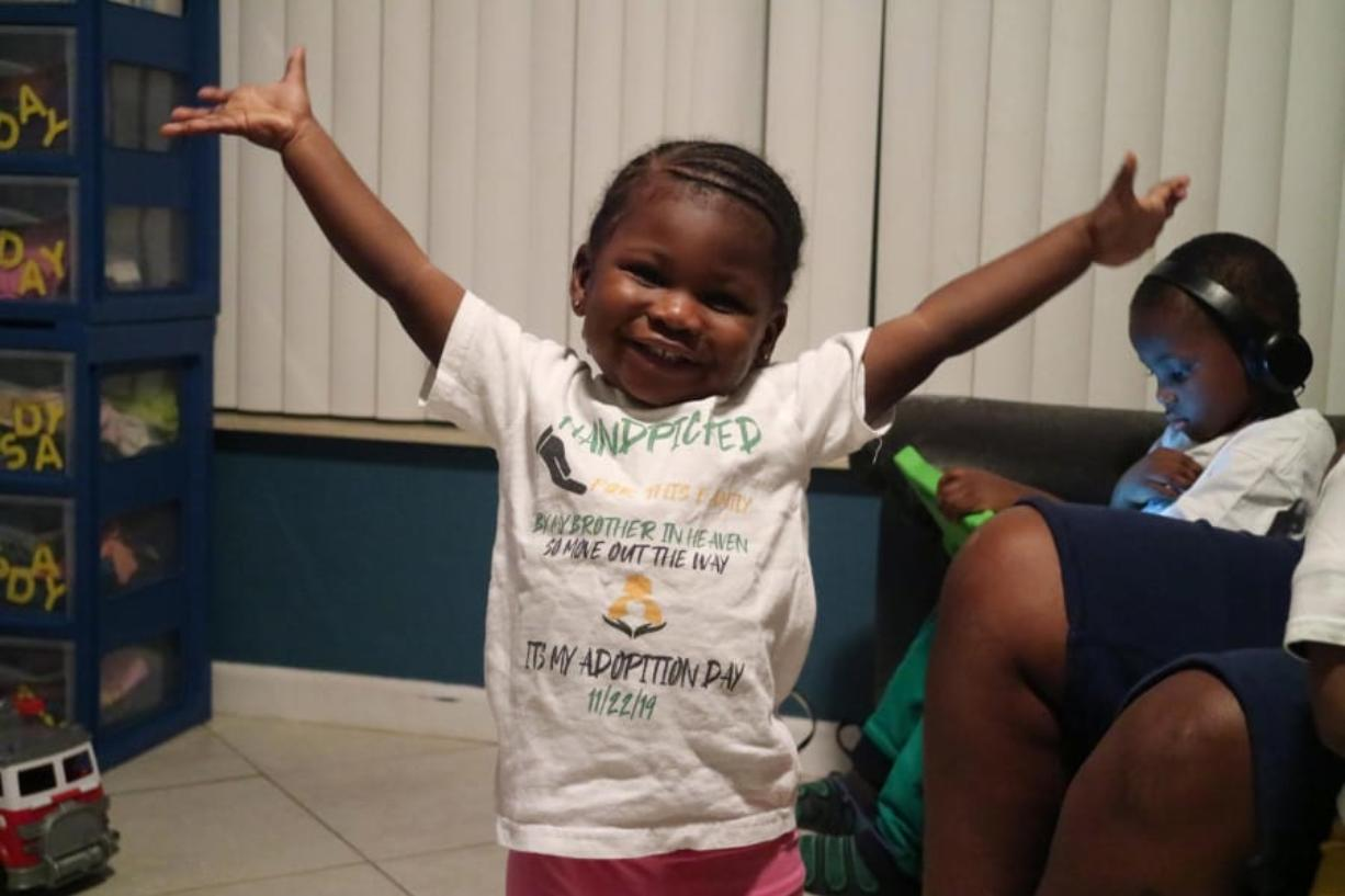 Two-year-old Zariah Senior smiles in her Boynton Beach home on Dec. 9. She is wearing the same shirt she wore on the day she and her siblings were adopted out of foster care by Monica Peoples and Michelle Senior. (Kristina Webb/Palm Beach Post/TNS)