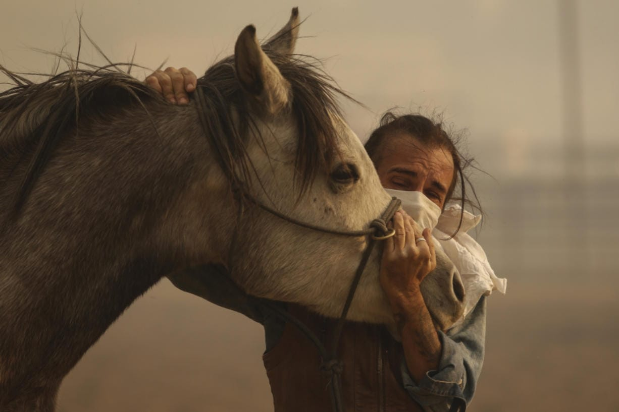 Fabio Losurdo comforts his horse, Smarty, at a ranch in Simi Valley, Calif., on Oct. 30. A brush fire broke out just before dawn in the Simi Valley area north of Los Angeles. (AP Photo/Ringo H.W. Chiu)