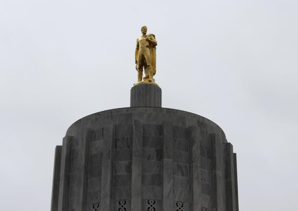 Oregon Pioneer, also known as Gold Man, is an eight-and-a-half ton bronze sculpture with gold leaf finish that sits atop the Oregon State Capitol in Salem, Ore. (Associated Press files)