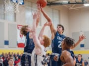 King's Way Christian's Justin Frahm, right, grabs a rebound over teammate Bryson Metz and Seton Catholic's Andrew Olson in the Knights' 75-65 win on Wednesday.