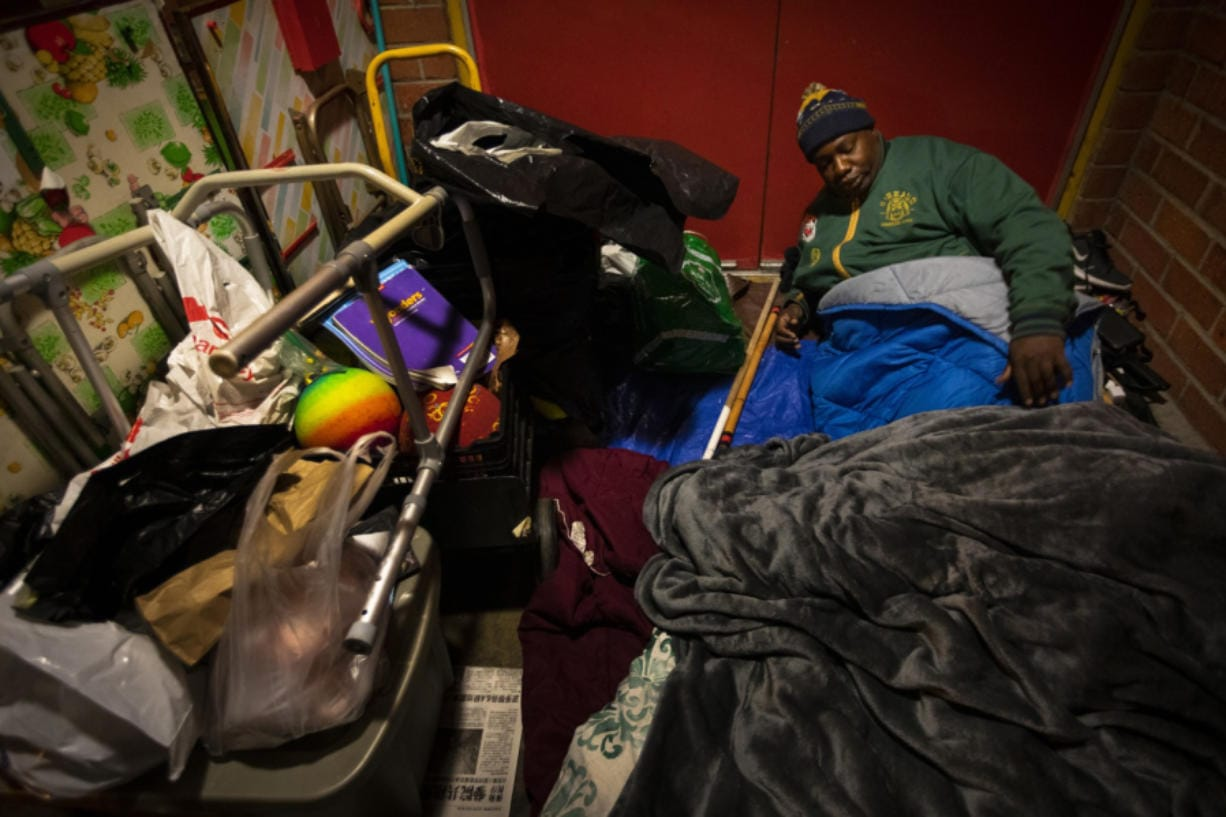 """Theodore Henderson, 46, beds down for the night in the Chinatown neighborhood of Los Angeles, Calif., on Jan. 8. It is cold and Henderson is living unhoused. He has a facebook group for the homeless community. In Los Angeles, Theodore Henderson called the group """"a respite to share our fears and not be castigated. When the former schoolteacher became ill, was evicted and ultimately ended up living in a park in Chinatown, he felt crushing shame. """"In the Facebook group, I encourage them and they encourage me,"""" said Henderson, who hosts a podcast called """"We the Unhoused."""" He started using the term 'unhoused' because 'homeless' was often being spat at him like a slur, he said."""