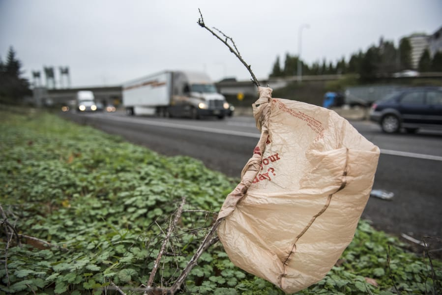 A plastic bag is stuck on a bush near passing traffic on Interstate 5 near downtown Vancouver. The Legislature is considering a bill that would ban single-use plastic bags at grocery store checkout lines and impose a fee on paper bags in order to encourage customers to switch to reusable bags.