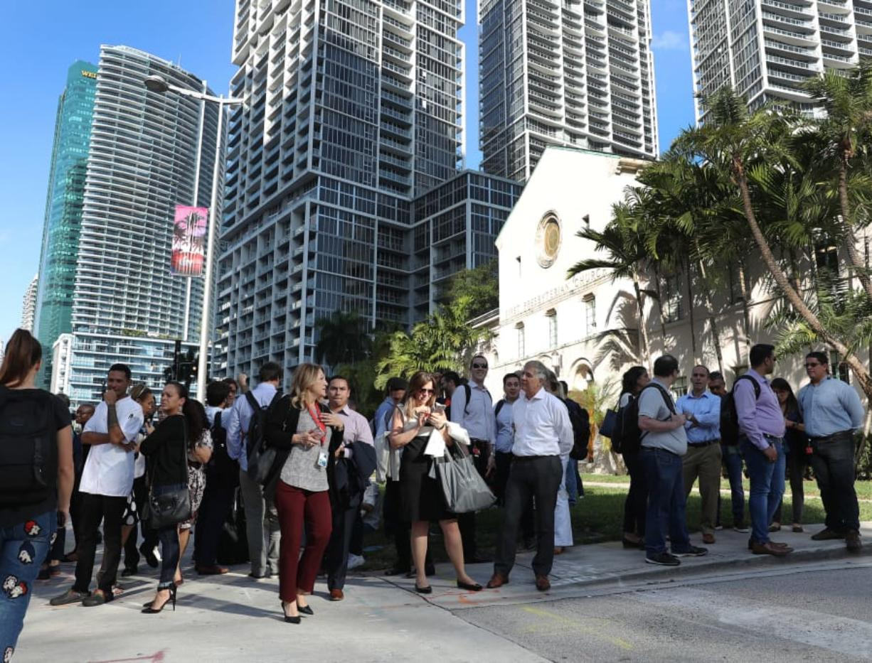 People wait outside after evacuating office buildings after an earthquake struck south of Cuba on January 28, 2020 in Miami, Fla. (Joe Raedle/Getty Images/TNS)