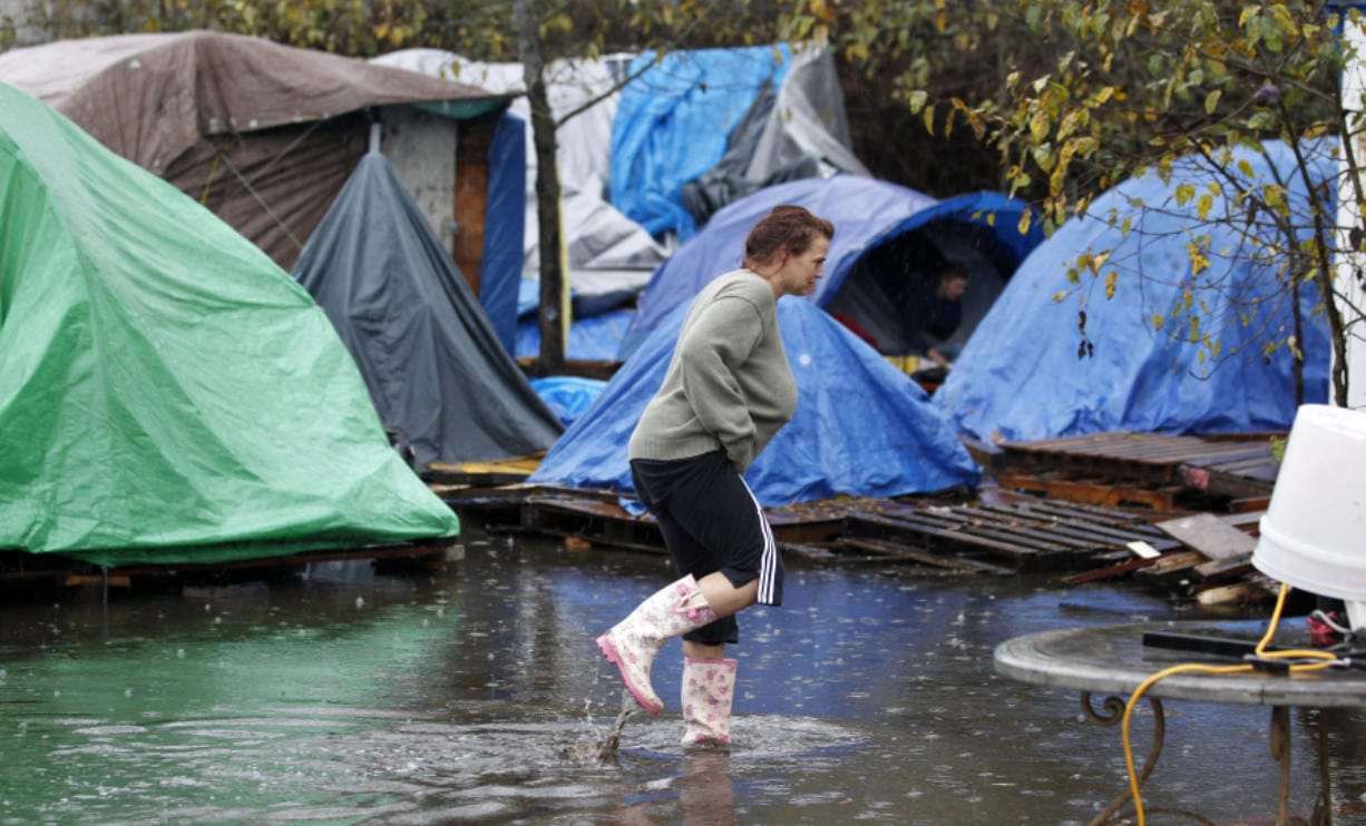Crystal Claflin wades past tents and through water in Nickelsville, a homeless encampment in Seattle in 2012 after a storm. (AP Photo/Elaine Thompson)
