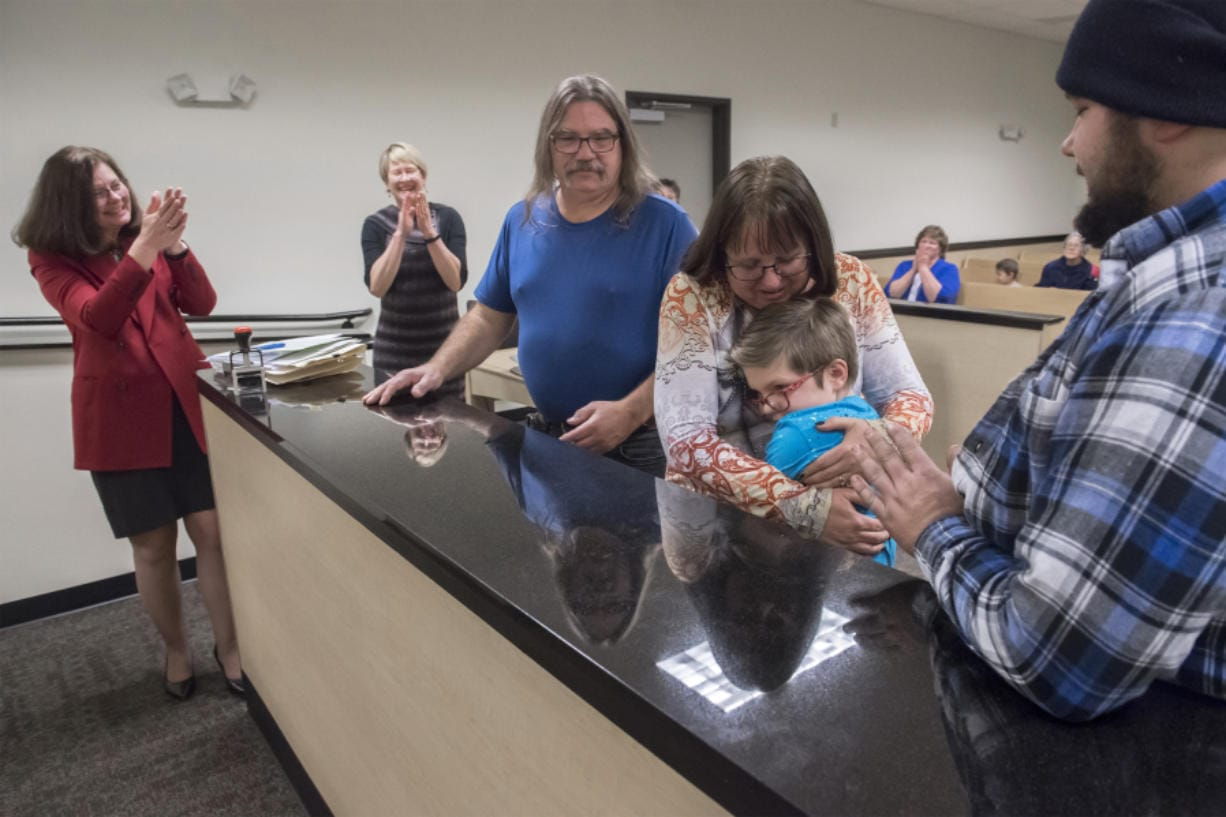 Shelly Krebs, the Bauer's attorney, from left, Kaine's Case Worker Jennifer Brinkman, Roddy Bauer, Crystal Bauer, Kaine Jackson Bauer, and Ronald Bauer, the Bauer's biological son, celebrate in the courtroom following Kaine's official adoption on Nov. 16, 2018. Crystal said Kaine insisted his name be changed to Michael Jackson following the adoption, but the Bauers convinced him to only change his middle name. (Nathan Howard/The Columbian)