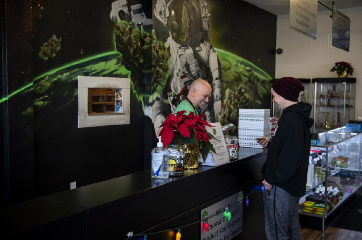 Charlie Gregory, budtender and cashier, helps Briana Reed of Vancouver finish her purchase at Main Street Marijuana in Vancouver on Dec. 12. (Alisha Jucevic/The Columbian)
