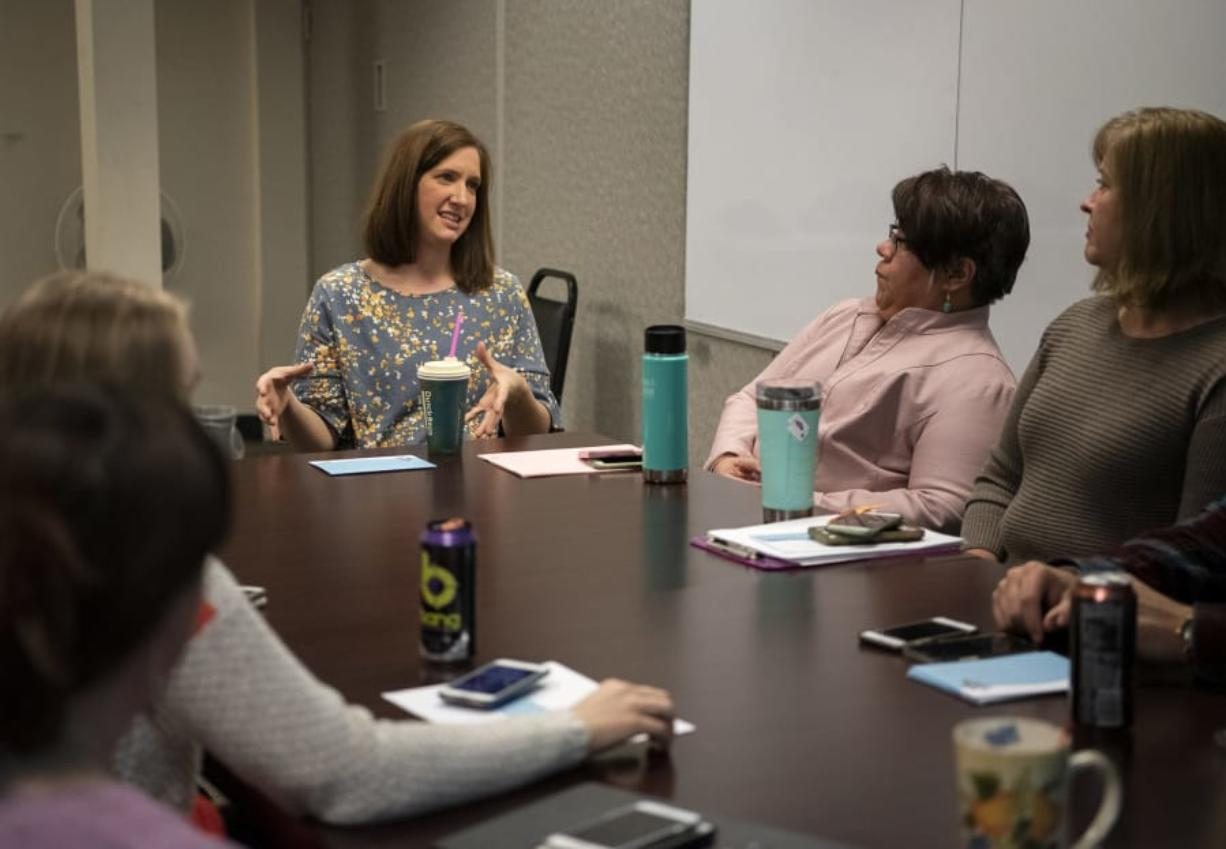 Clinical supervisor Brook Vejo, center, talks with the Youth Mobile Crisis Intervention team during its meeting at Catholic Community Services in Vancouver. The organization works with teenagers who are in a mental health crisis in an effort to keep them out of the emergency room.