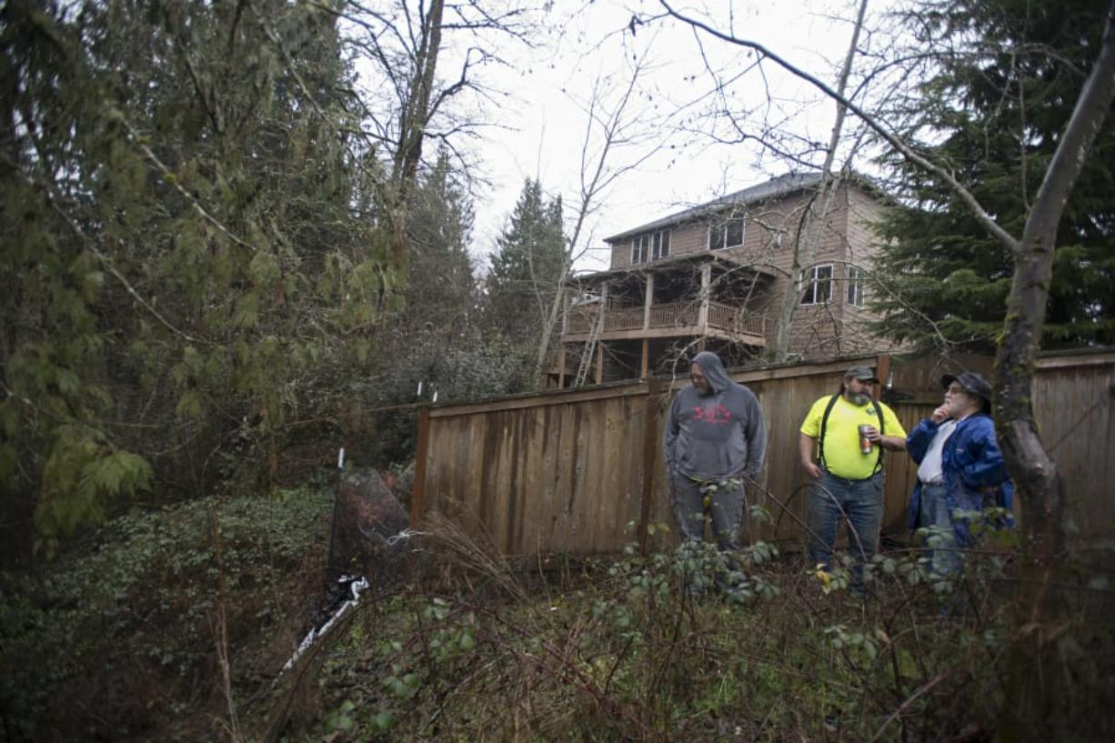 J.R. Ramsey, from left, and Guy Price of Advanced Earth Stabilization consult with homeowner Richard Schwartz of Ridgefield about the landslide in his backyard. Schwartz has been trying to get his yard fixed for more than two years after heavy rain and a neighboring stormwater pond caused a landslide on the hill behind his house.