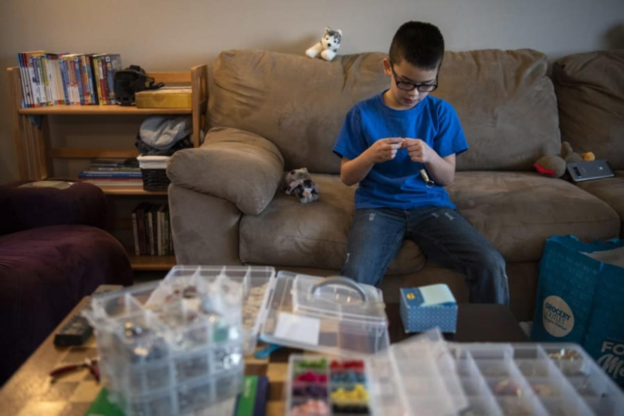 Keoni Ching, 8, demonstrates how he makes keychains Friday morning at his home in Battle Ground. Last month, Keoni started making keychains to raise money to pay off students' unpaid lunch accounts at his school, Benjamin Franklin Elementary School. He's raised nearly $1,000.