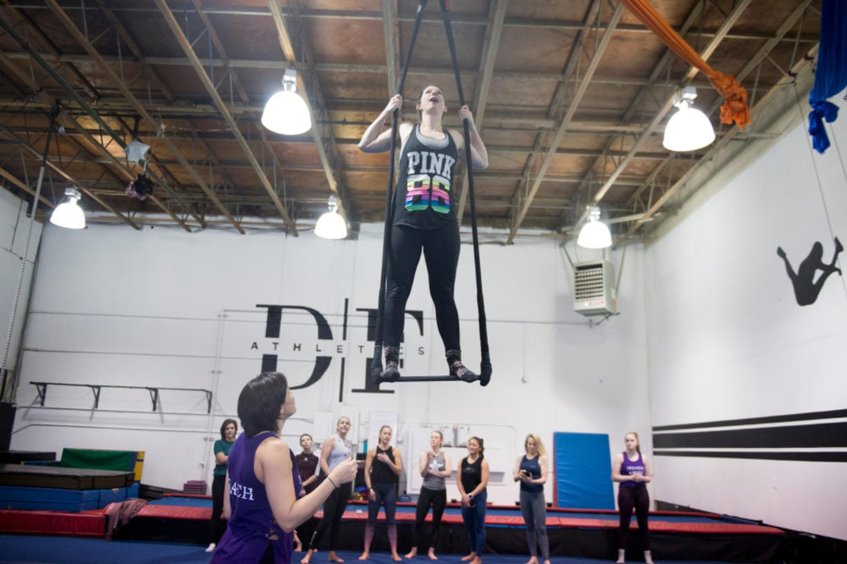 Kelley Baker stands on top of the bar during a Saturday adult trapeze class by Premier Cirque in Hazel Dell. (Samuel Wilson for The Columbian)