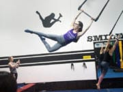 Brittany Ashworth, owner of Premier Cirque in Hazel Dell, swings during a Saturday trapeze class. She founded the business because she was tired of commuting to classes in Portland.