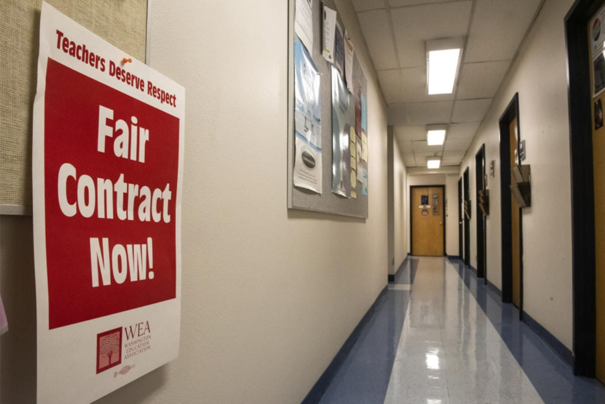 A poster signaling support for the Association for Higher Education hangs in a hallway of faculty offices in Foster Hall at Clark College on Monday afternoon. Faculty are poised to strike Jan. 13 if a deal is not reached between the union and college administration.